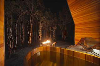 Guests unwind in the cedar ofuro soaking tub, overlooking the blazing fire pit and dense forest.