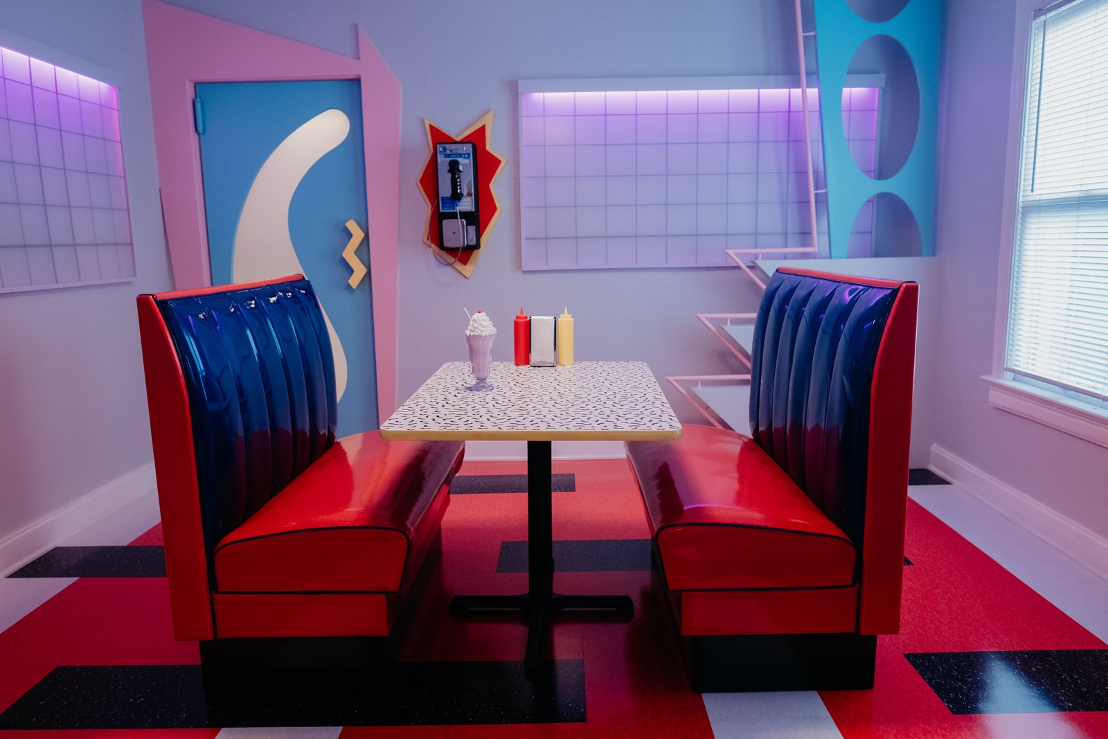"""Dining Room, Table, and Bench The Slater's dining area cleverly re-creates the Max, the hangout frequented by Bayside High students on Saved by the Bell.   Photo 1 of 13 in Relive the '90s in This """"Saved by the Bell""""-Inspired Dallas Airbnb"""