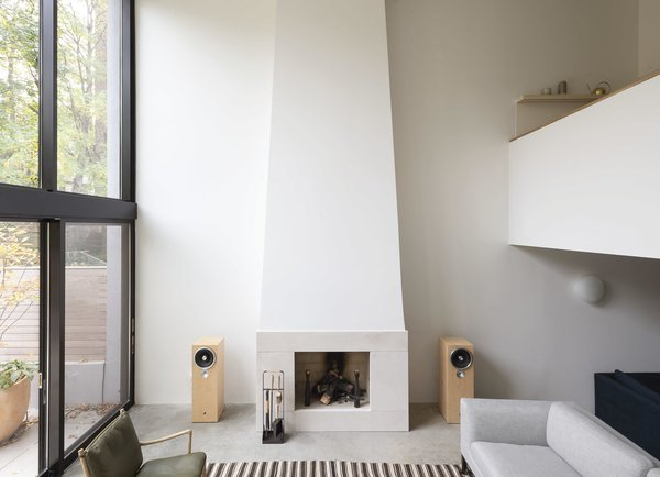 The fireplace, flanked by speakers, is a central feature of the living room.