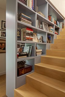 A bookcase adds visual intrigue to the staircase connecting the lower level to the master suite.