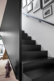 Black metal and wood define this staircase leading to the guest suite over the garage.