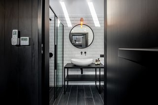 In the bathroom, white tiles punctuate the largely black bathroom, a twist on the house's overall black-and-pine juxtaposition.
