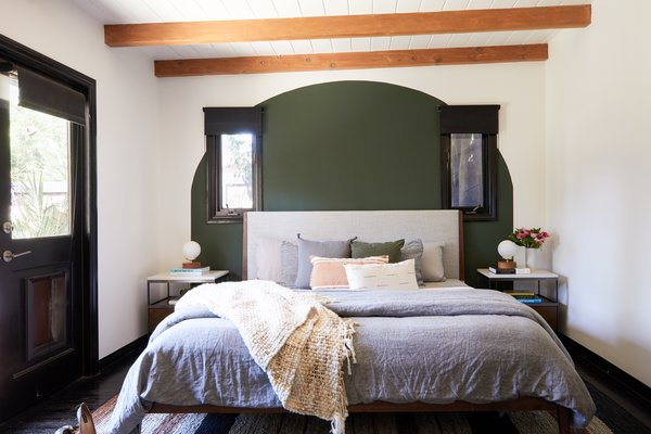 Rustic wood beams and a painted green arch create a soothing background for the master bedroom. Here, like the guest room, the bed is from Inmod.