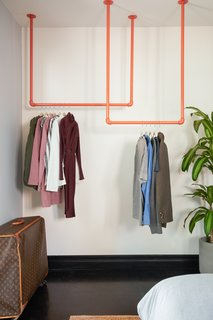Clothes are hung on an inviting set of orange-painted pipes in the guest bedroom.