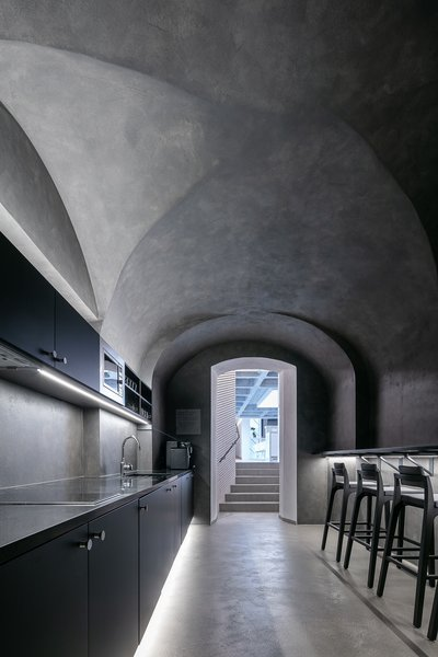 Lasvit staff break for coffee in this dark-hued space with the stand-out vaulted ceiling.