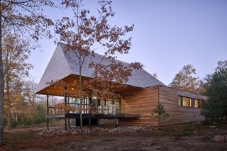The glass pavilion rises into a peaked roof, one of the cabin's most distinguishing features.