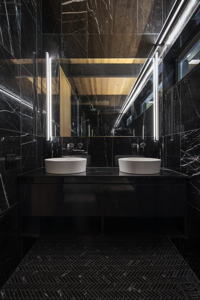 Linear lighting accentuates the black Spanish marble dominating a bathroom that once flaunted pastel ceramics.