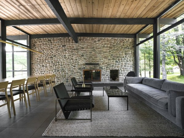 "Blouin and Dupont kept the river rock surrounding the fireplace despite its loud texture ""because the smoothness, or overall materiality of the house, gives a sense of balance to the living room,"" says Blouin."