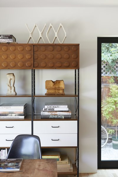 Adjacent to the dining table, art books and sculptures get the spotlight.