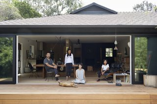 The Yanai-Rhee family gathers on the deck, an organic transition between the house and the garden. The exterior, now painted black, is reminiscent of the Japanese shou sugi ban technique.
