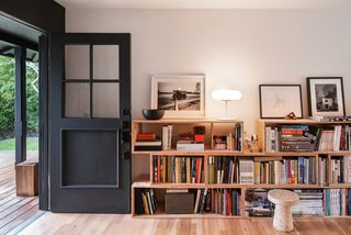 Shelves, filled with books and objects, are a focal point of the living room.