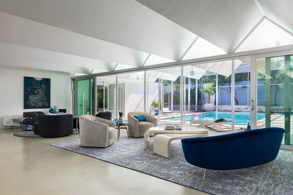 """A painting by Taiwanese artist James Jean is a focal point in the main living area, where low ceilings, common to architecture of the era, led interior designer Jennifer Masters to select furniture that sits at a lower height """"without sacrificing comfort."""" Bonus: unimpeded views of the pool."""