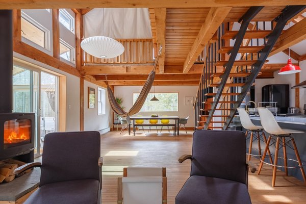 """With a record playing in the background, gaze at bluestone boulders from the couch, then revive with a coffee made in the marble counter-topped galley kitchen at this post and beam saltbox cabin in Bearsville. It embraces an open-plan, loft-living layout, but contemplative moments abound—at the writing nook, on the glassed-in porch or sprawling deck, and in the beds enveloped by canvas """"walls."""" Reward visits to Cooper Lake and the Mink Hollow hiking trail with a snooze on the central hammock, a Noguchi light fixture above."""