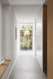 Punctuating a hallway with light was among the clients' few requests for the house. EFFEKT achieved it through a panel of glass that highlights a swath of greenery.