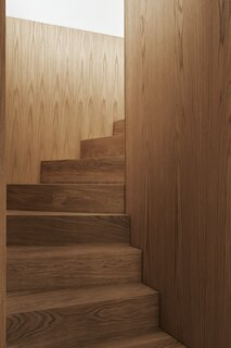 The sculptural oak staircase reinforces the villa's predilection for simplicity and natural materials.