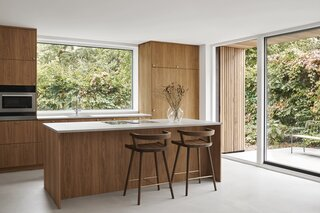 Oak and concrete surfaces mingle in the kitchen, where views of the landscape are framed through a window and the sliding glass door that opens onto the cedar-clad patio.