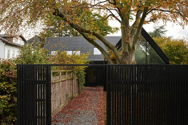The modern dwelling incorporates its woodsy-yet-urban surrounds through copious glazing.