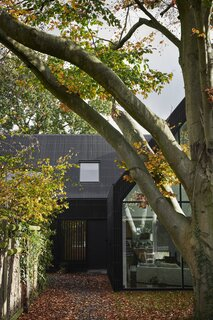 The facade, defined by a wall of glass on one end of the L-shaped dwelling, illuminates the muted living area.