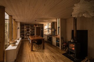 The cabin, comprised of just wood and glass, feels especially cozy when the stove is lit.