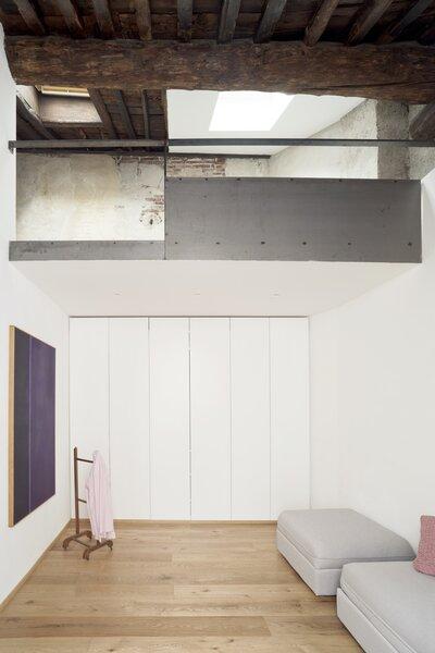 A Ferdinando Maffii painting hangs beside a sleek, custom wardrobe.