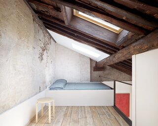 The stripped-down, lofted bedroom is tucked under a slanted roof with generous skylights. Dating from the second half of the 17th century, the wooden ceiling expresses ancient construction techniques that draw from naval culture, recalling the masts of dismantled boats.