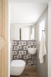 Tiles from an 18th-century Naples factory add pattern to a compact bathroom.