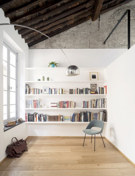 The reading room's custom bookcase is made of white lacquered wood. A vintage chair and an Arco lamp from FLOS create a cozy, illuminated nook.