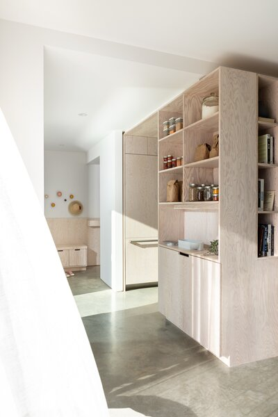 """Open plywood shelving in the kitchen sets a tone for the rest of the house. """"The mandate for the materials was modesty,"""" explains Cuddington."""