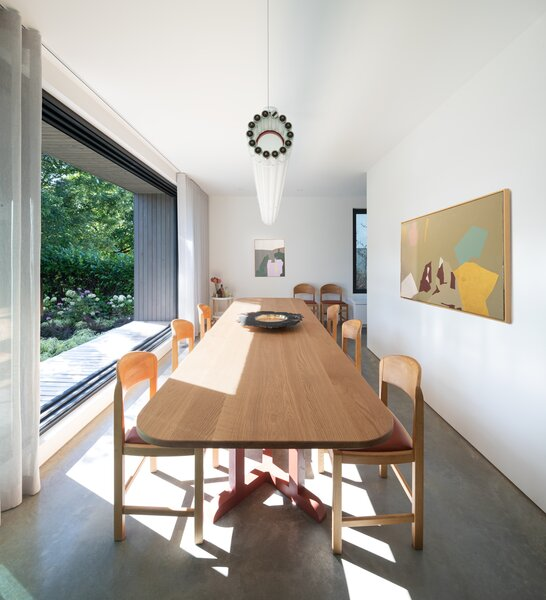 The sun-drenched dining room features a commodious table designed by Measured Architecture and fabricated by local studio Caliper, surrounded by restored vintage Danish chairs.