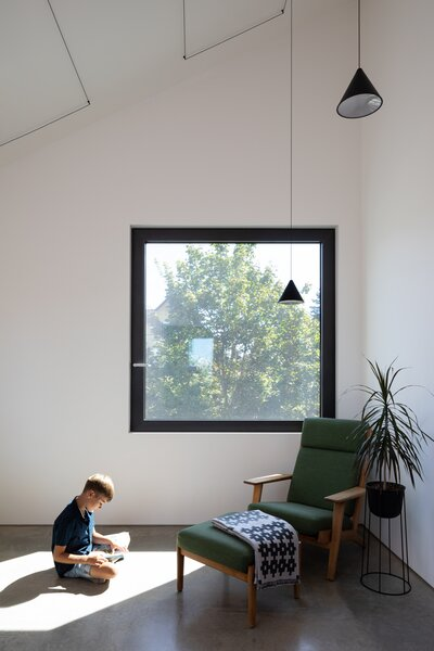 Views of neighboring trees fill the office, where the color green also manifests in a vintage Hans Wegner armchair and ottoman.