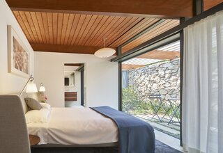 Small patios with bistro folding chairs adjoin each bedroom, filling the spaces with natural light.