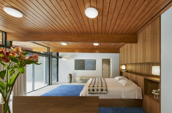 Custom walnut millwork, courtesy of Brininstool + Lynch, provides a crafted, minimalist touch in the bedroom that overlooks the pool.