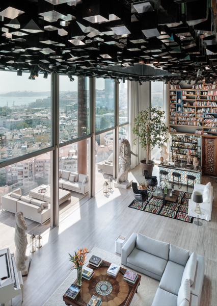 The common area in this penthouse by Studio RHE boasts a digital cube ceiling, stunning views, and an immense book collection by the bar.