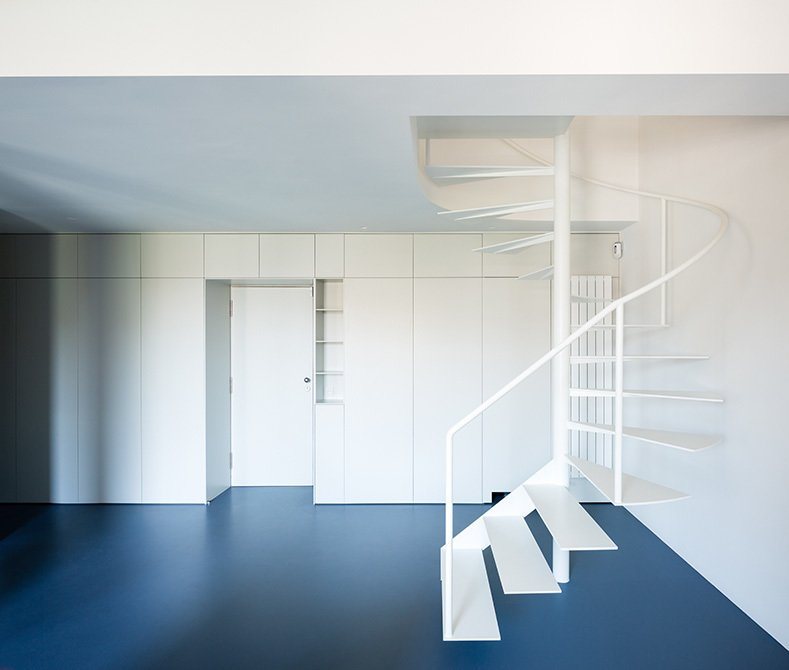 Staircase, Metal Tread, and Metal Railing The main access to the loft is through an architectural piece of furniture shaped as a thick wall that integrates facilities and storage inside.  Photos