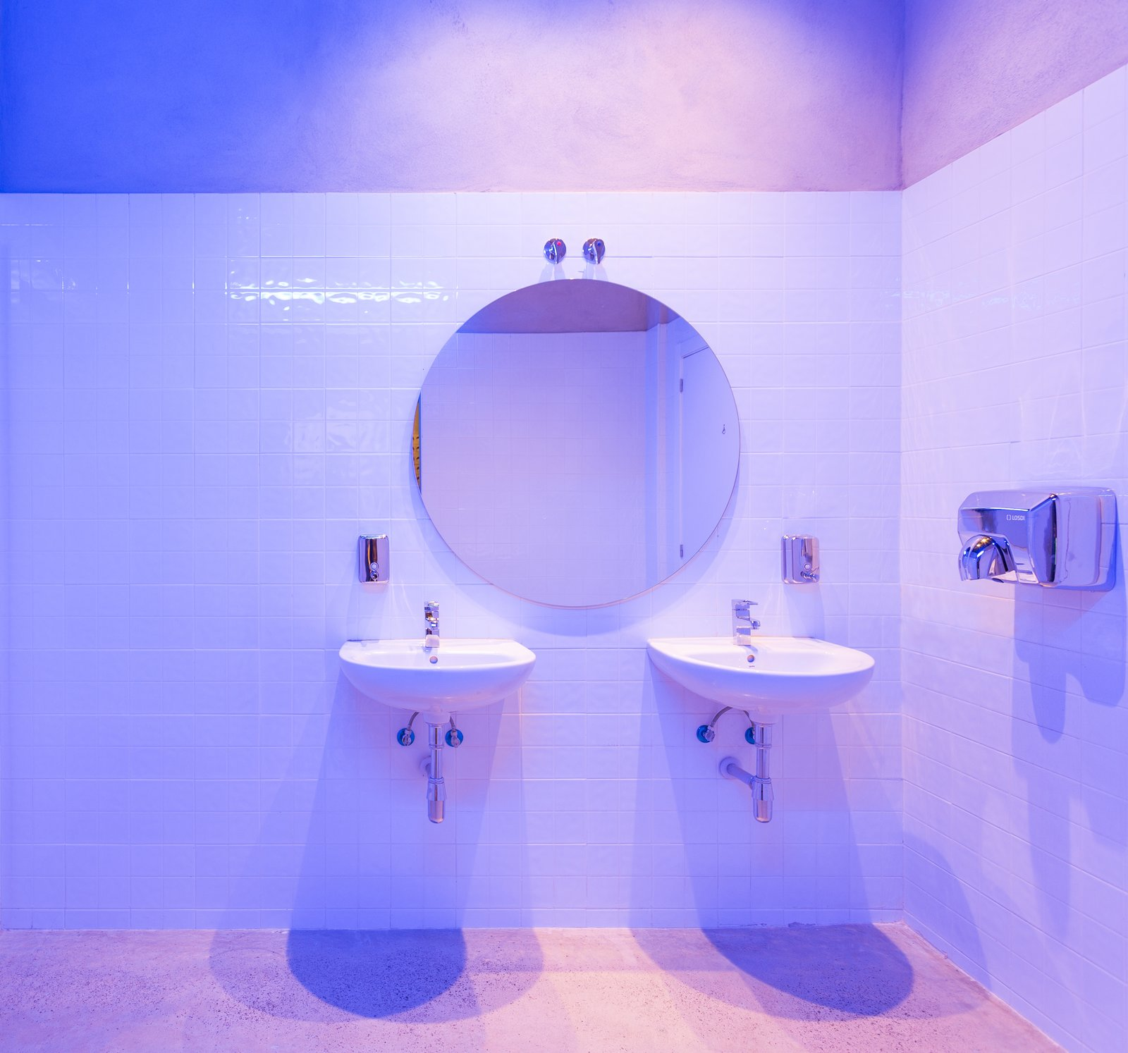Bath Room, Concrete Floor, Recessed Lighting, Accent Lighting, Ceramic Tile Wall, Wall Mount Sink, and Ceiling Lighting The lighting in the bathroom creates suggestive blue gradients.  IMOOD Restaurant