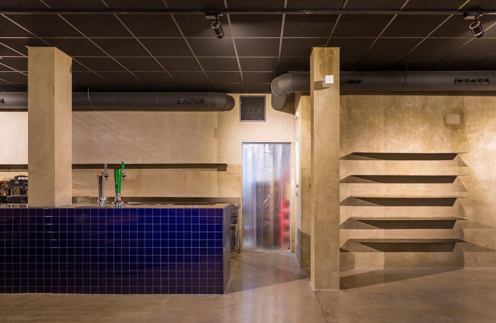 Kitchen, Tile Counter, Track Lighting, Wall Lighting, Accent Lighting, Concrete Floor, and Ceramic Tile Backsplashe The cobalt blue ceramic coated bar emerges from the floor.  IMOOD Restaurant