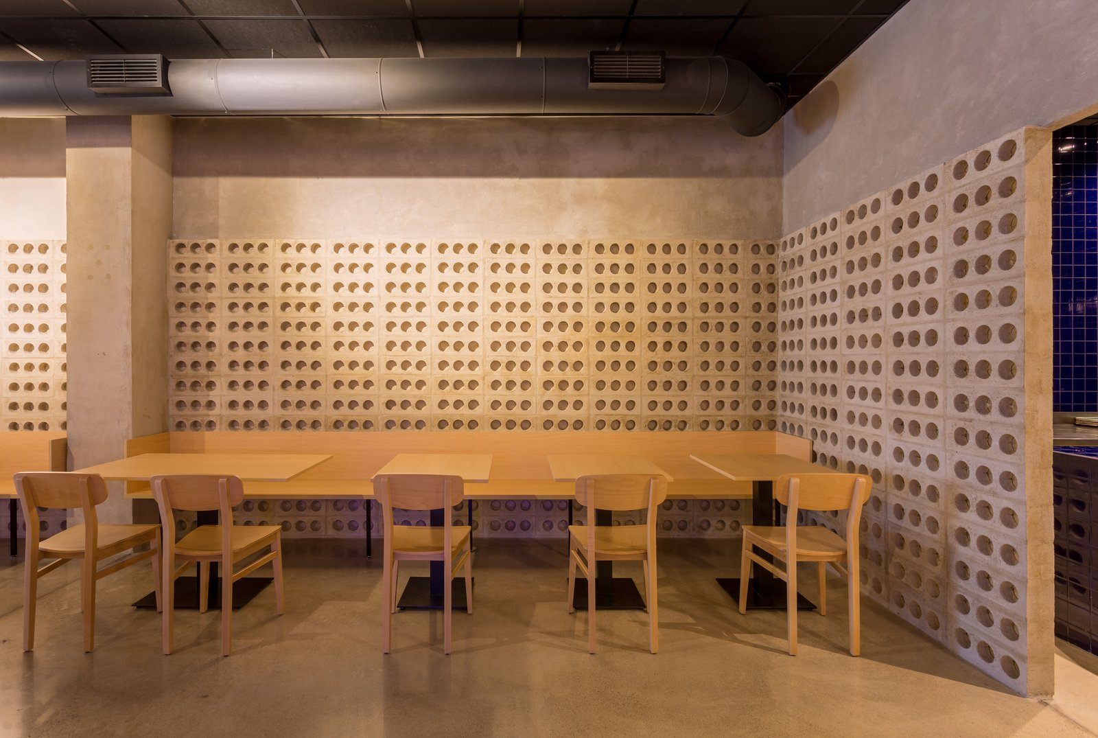 Dining Room, Track Lighting, Chair, Concrete Floor, Table, Bench, and Ceiling Lighting The wooden furniture contrasts with the roughness of the cement.  IMOOD Restaurant