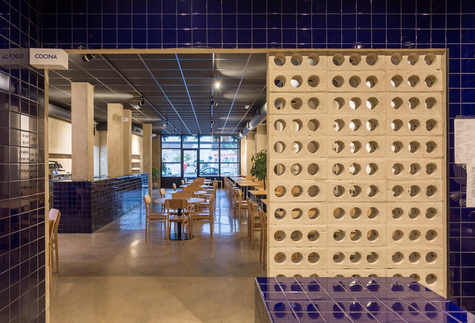 Kitchen, Tile Counter, Concrete Floor, Ceramic Tile Backsplashe, Accent Lighting, Ceramic Tile Floor, Wall Lighting, Ceiling Lighting, and Track Lighting The latticework suggests transparencies from the kitchen.  IMOOD Restaurant