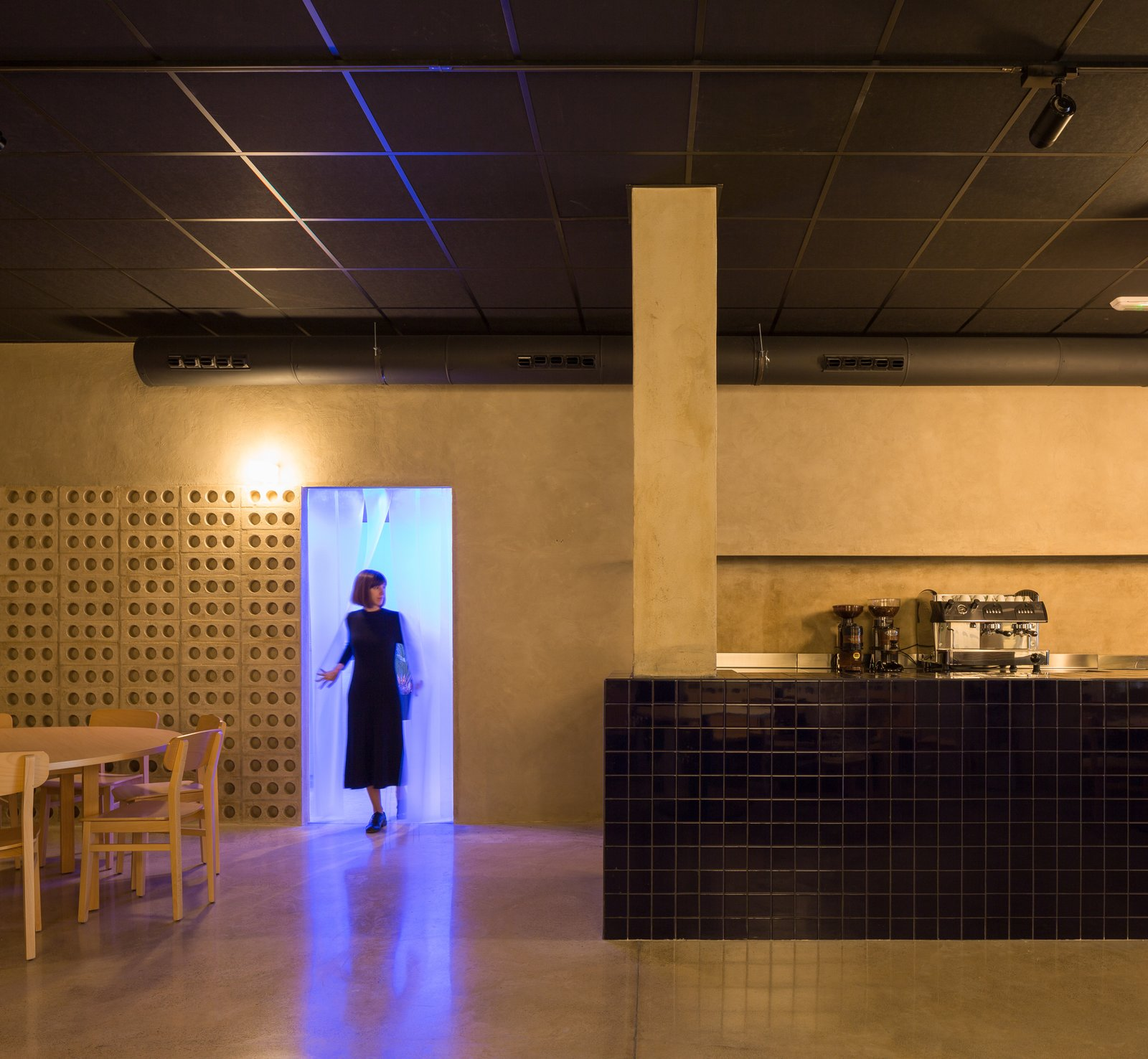Kitchen, Tile Counter, Ceramic Tile Backsplashe, Concrete Floor, Wall Lighting, Accent Lighting, and Track Lighting The translucent PVC slats are the entrance to the toilet.  IMOOD Restaurant
