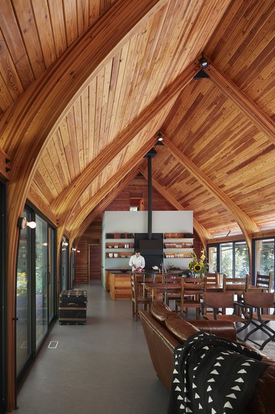 """""""Sharing roots with local Michiana pole barns, this economical structure of glue-laminated Douglas fir bents, braces, and decking is held above runoff and snow by galvanized steel stirrups,"""" says Wheeler Kearns Architects. The boat-like, wooden ceiling in Bohan Kemp is a truly unique feature, directing air flow and adding charm to the space."""