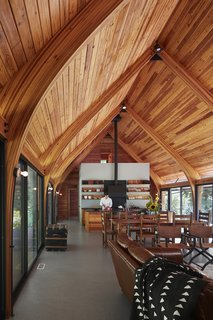 """Sharing roots with local Michiana pole barns, this economical structure of glue-laminated Douglas fir bents, braces, and decking is held above runoff and snow by galvanized steel stirrups,"" says Wheeler Kearns Architects. The boat-like, wooden ceiling in Bohan Kemp is a truly unique feature, directing air flow and adding charm to the space."