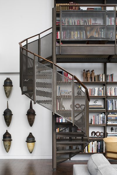 Wheeler Kearns Architects used steel to construct the shelving, storage, and stairs leading up to the mezzanine loft in the Residence for Two Collectors. The client's father was a machinist, so the fabrication of these elements lends a personal touch to the project.