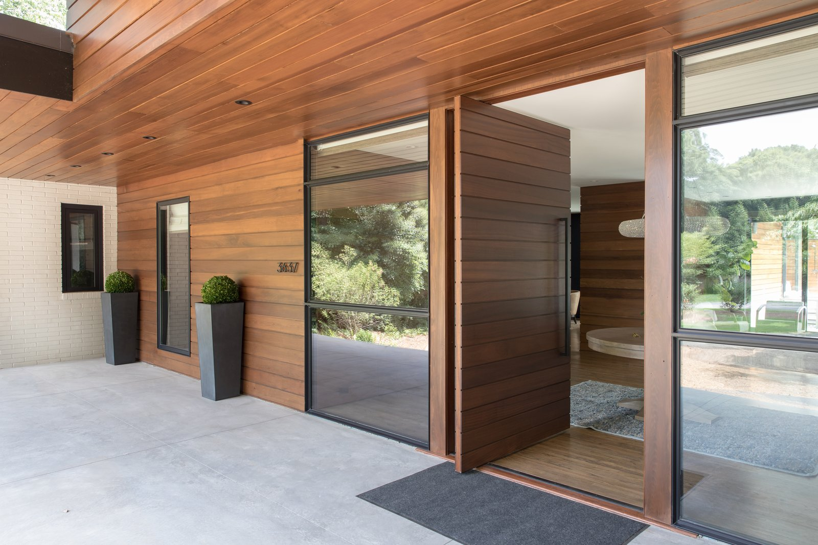 Exterior, Metal Roof Material, Mid-Century Building Type, Hipped RoofLine, and Wood Siding Material Custom pivot door at home's entry  Guinn/Henderson Residence