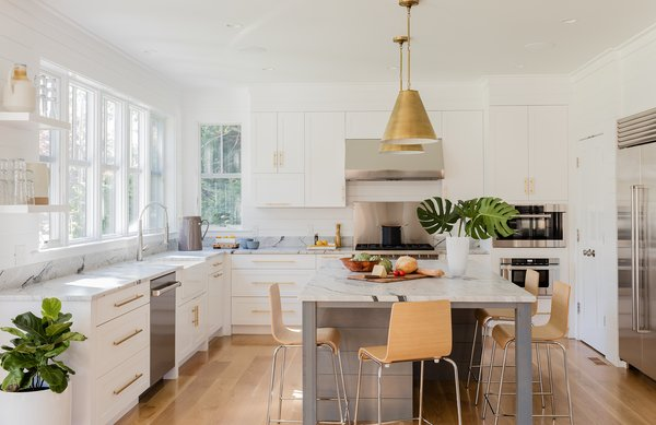 Custom cabinets, shiplap, and warm brass tones make this kitchen by Hawthorn Builders very inviting and clean.