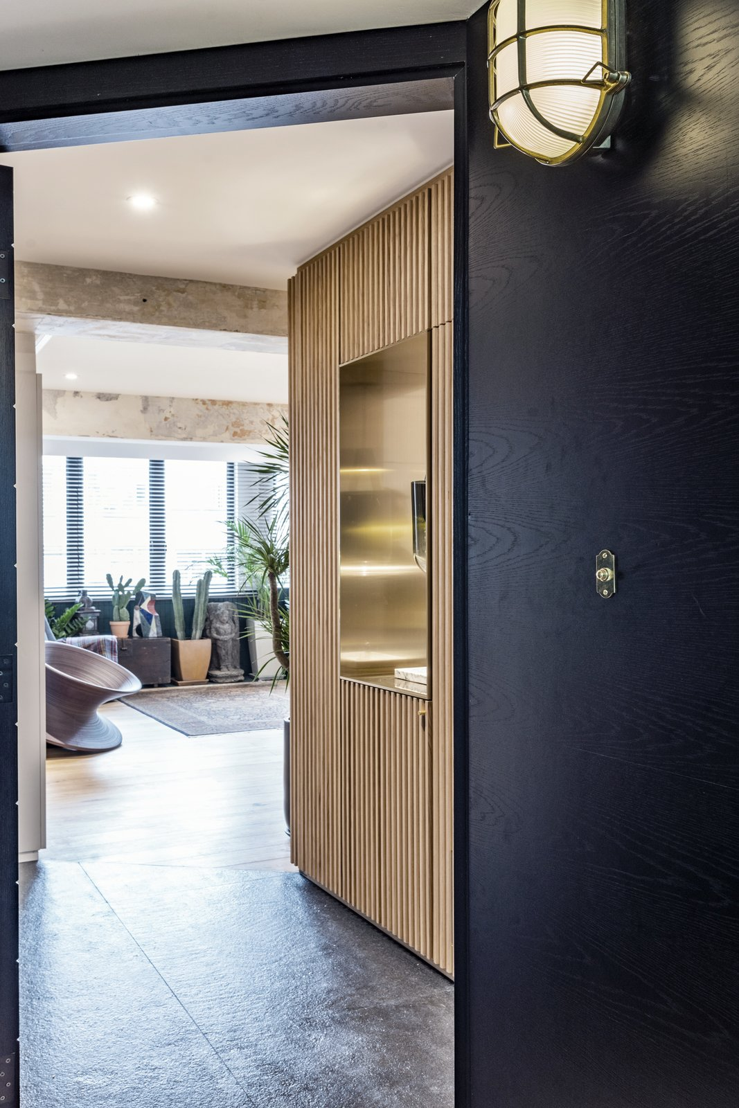 Hallway and Slate Entry area- a shoe storage with wood slat panels and a brass punch out to frame the view into the kitchen  Hallway Slate Photos from Quarry Bay Residence