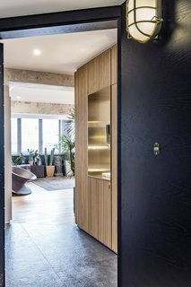 Entry area- a shoe storage with wood slat panels and a brass punch out to frame the view into the kitchen