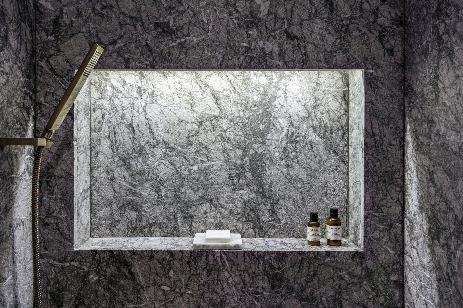 Enclosed Shower, Ceramic Tile Floor, Marble Wall, and Accent Lighting Built-in shelving in the master shower area with grey marble   Photos from Quarry Bay Residence