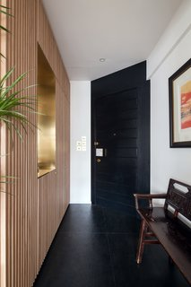 The entryway of Quarry Bay Residence greets visitors with a full-height oak slat shoe closet with a cutout finished in brass. Lim + Lu took great care to ensure that the interior of the apartment has sweeping views from one room to another.