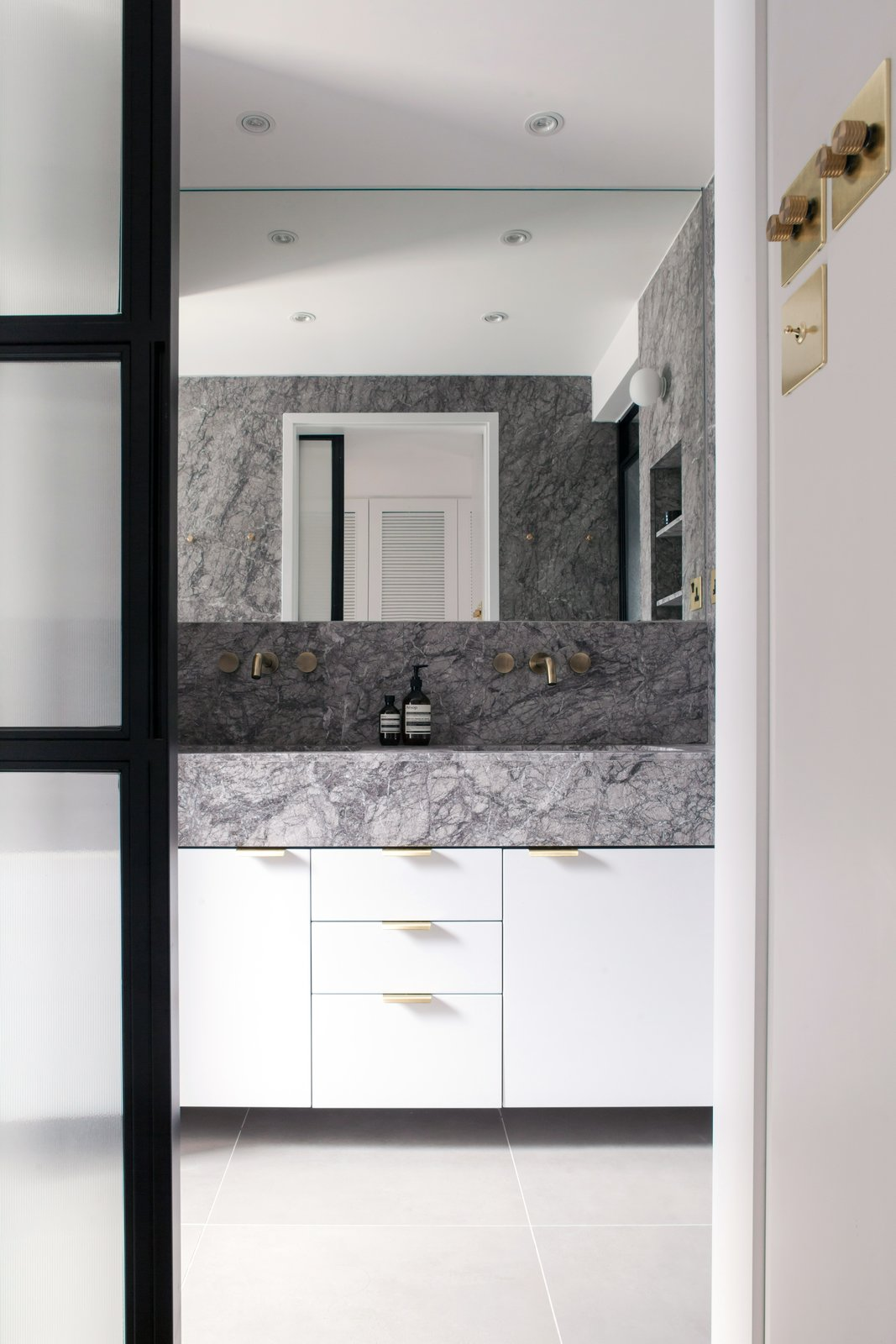 Bath Room, Marble Wall, Drop In Sink, Marble Counter, Wall Lighting, Enclosed Shower, Recessed Lighting, and Ceramic Tile Floor Grey marble, white wood, black metal and glass doors, along with brass accents, creates a contemporary and calming master bathroom.  Quarry Bay Residence by Lim + Lu