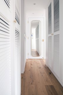 An all-white walk-in closet design creates a brighter and more expansive perception of the space